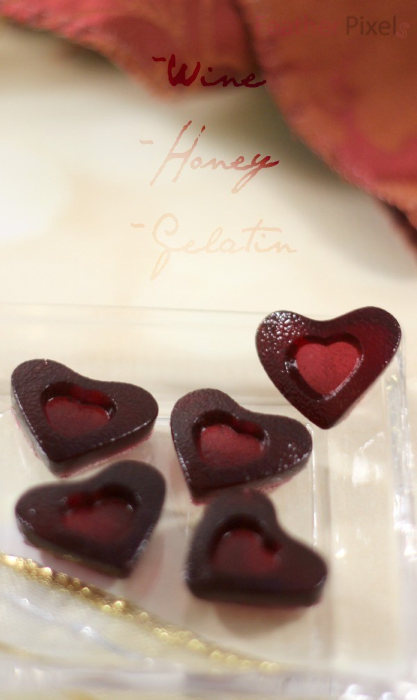 Red wine gummies in heart shapes on a tiny dish