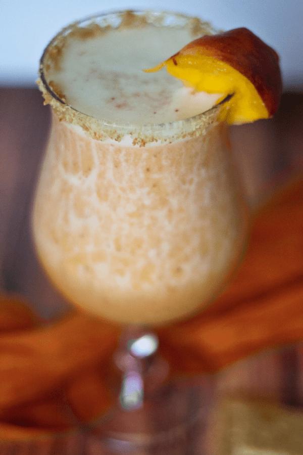 Peach Cobbler Margarita in a glass with a fresh peach garnish