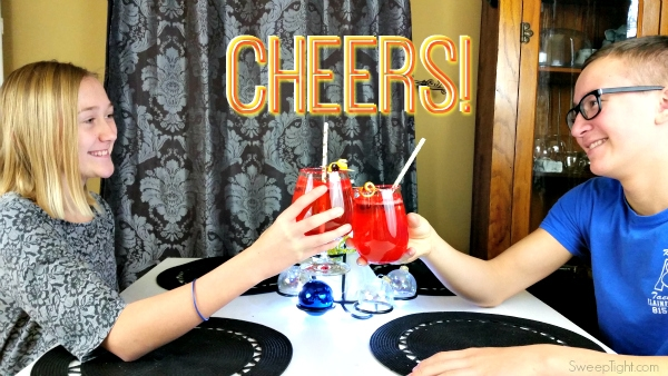 Two kids holding glasses to cheers a sparkly red kid-friendly drink
