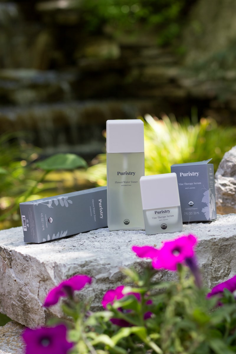 Puristry Organic Toner and Resveratrol Skin Care products on a rock outside