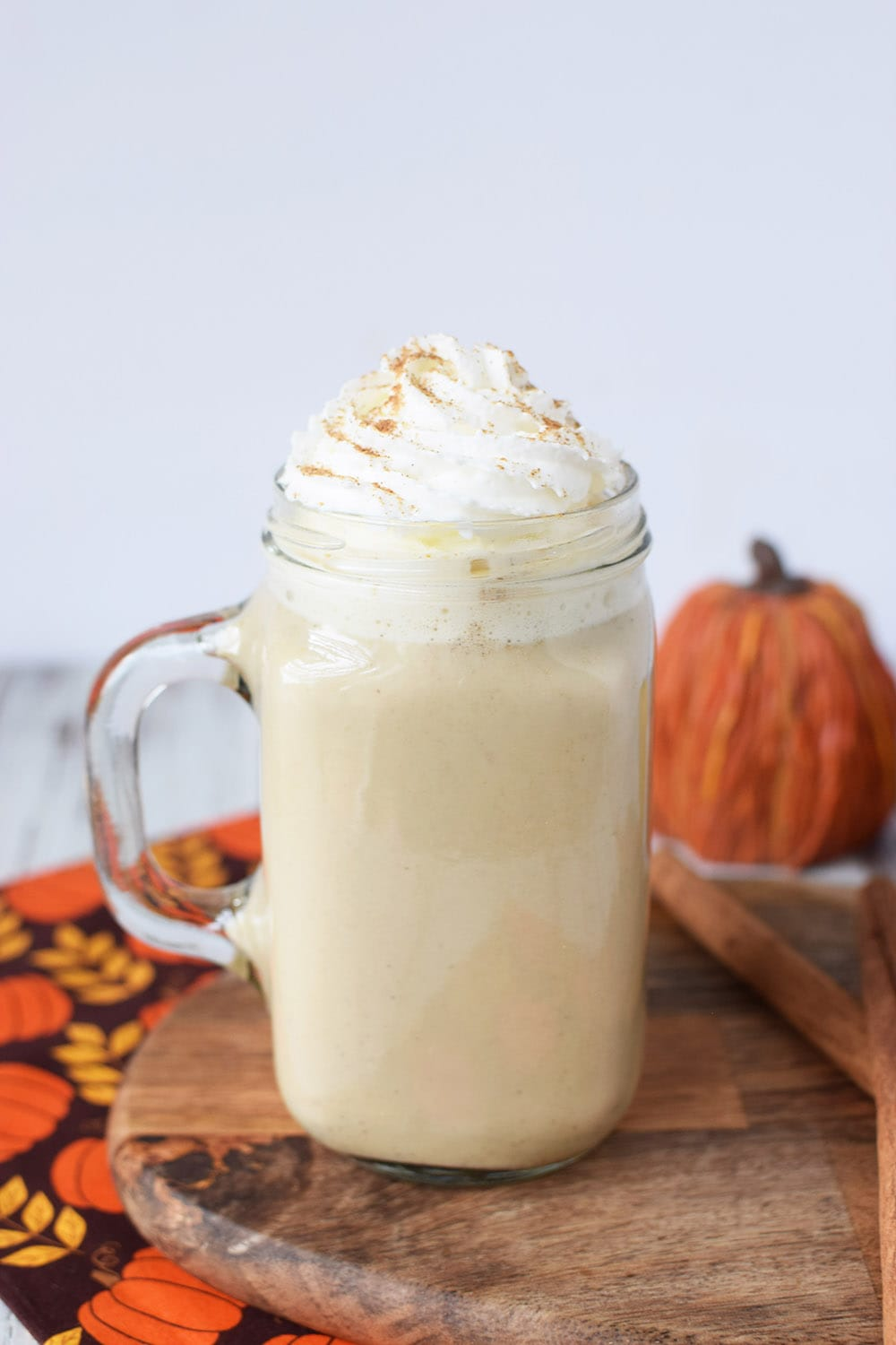 Pumpkin spice latte topped with whipped cream and cinnamon sitting by pumpkins