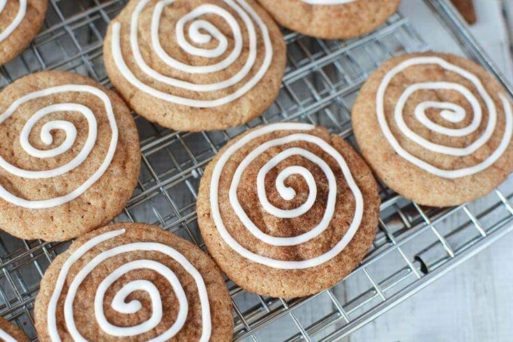 Cinnamon cookies on a baking rack with icing swirl