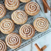 Cinnamon cookies with icing swirl on rack with cinnamon sticks