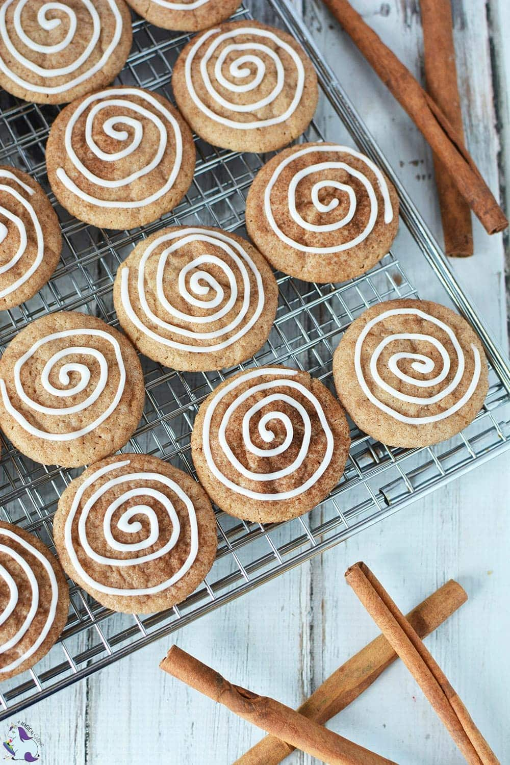 Cinnamon cookies with icing swirl on rack with cinnamon sticks