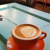 latte in an orange mug on a light blue table