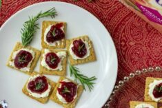 Cream cheese, cranberry jam, and fresh rosemary on a Triscuit