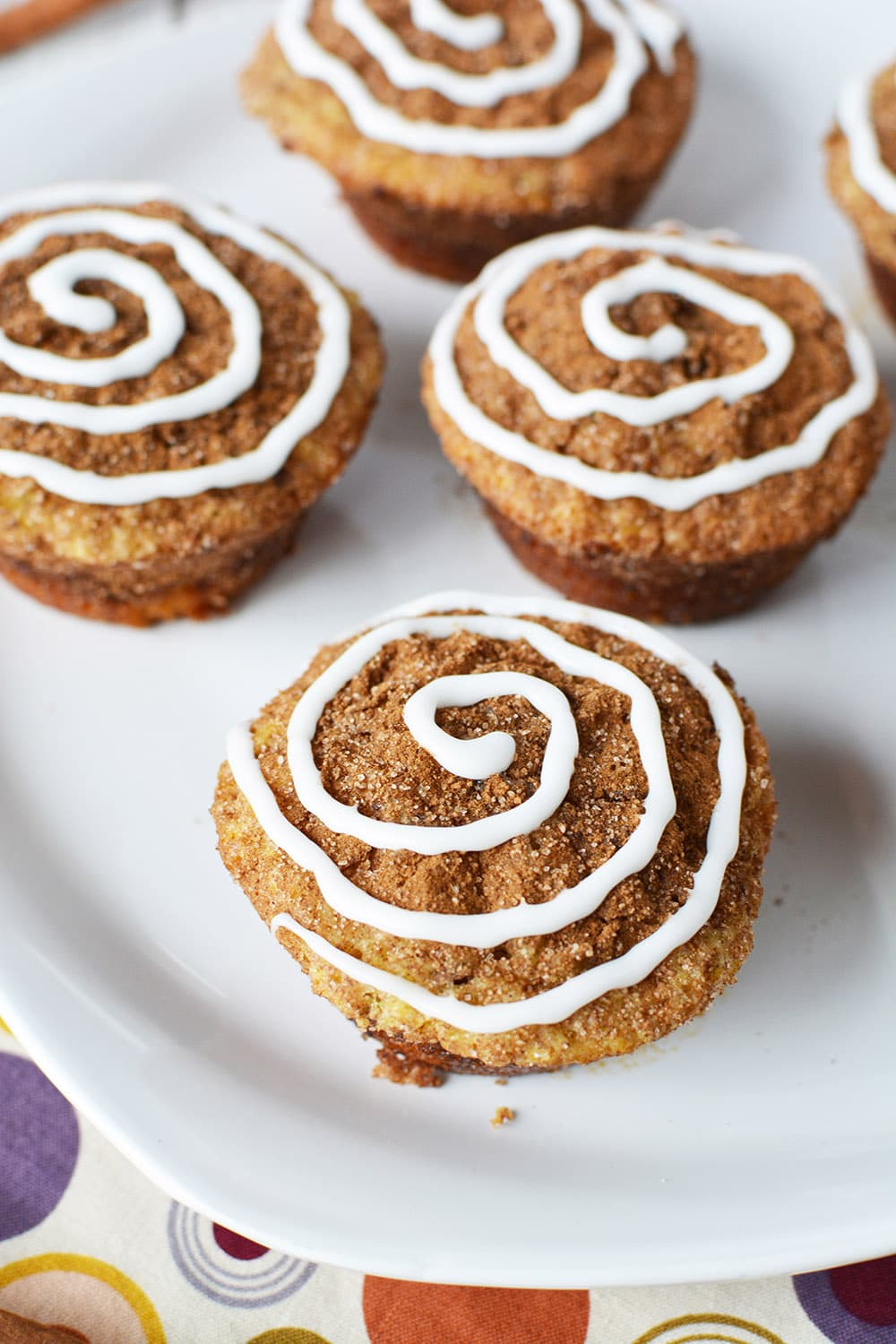 Cinnamon muffins on a plate. Cinnamon topping and icing swirl to give cinnamon roll appearance.