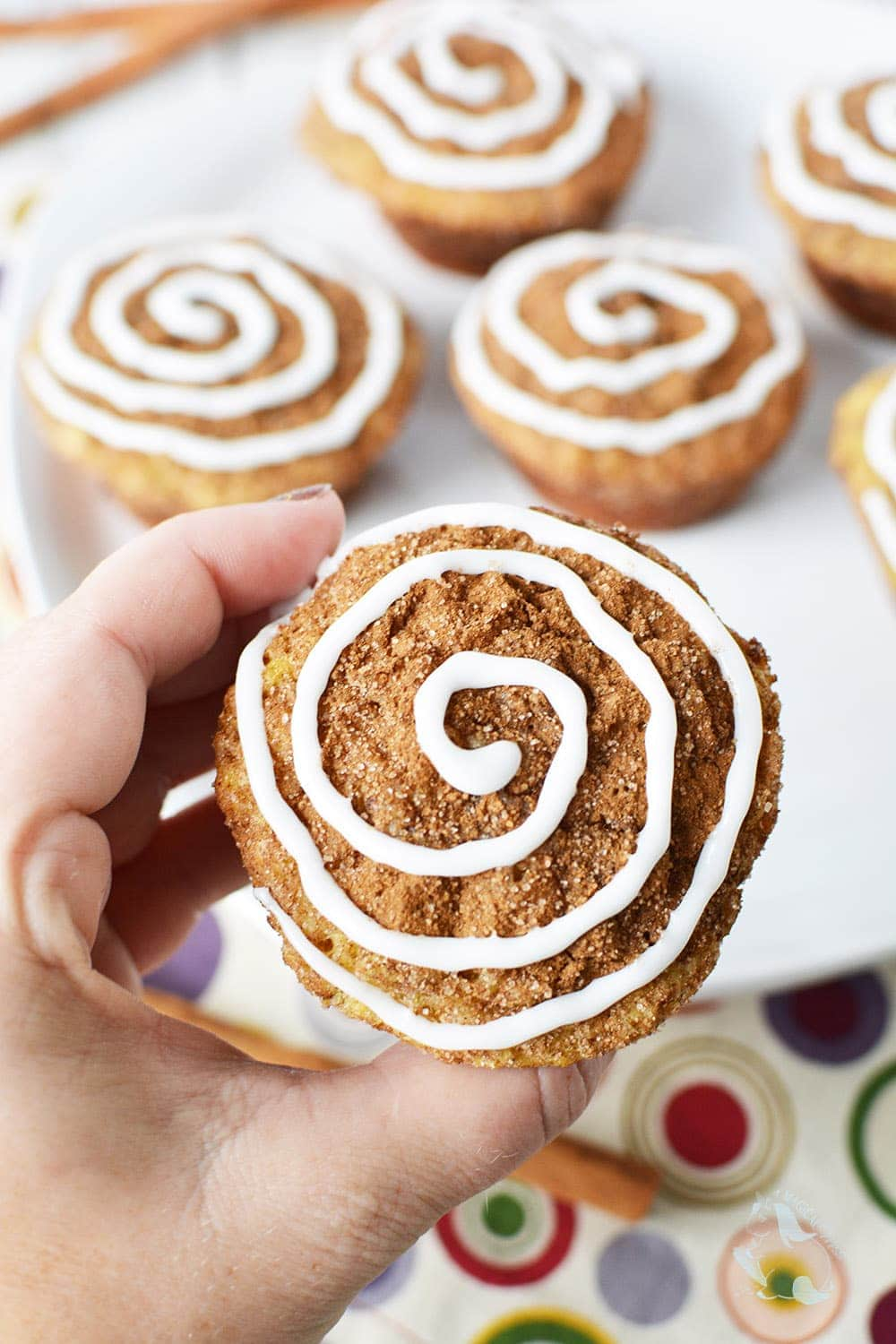 Holding a cinnamon roll muffin up to get a closer look of the glaze topping.