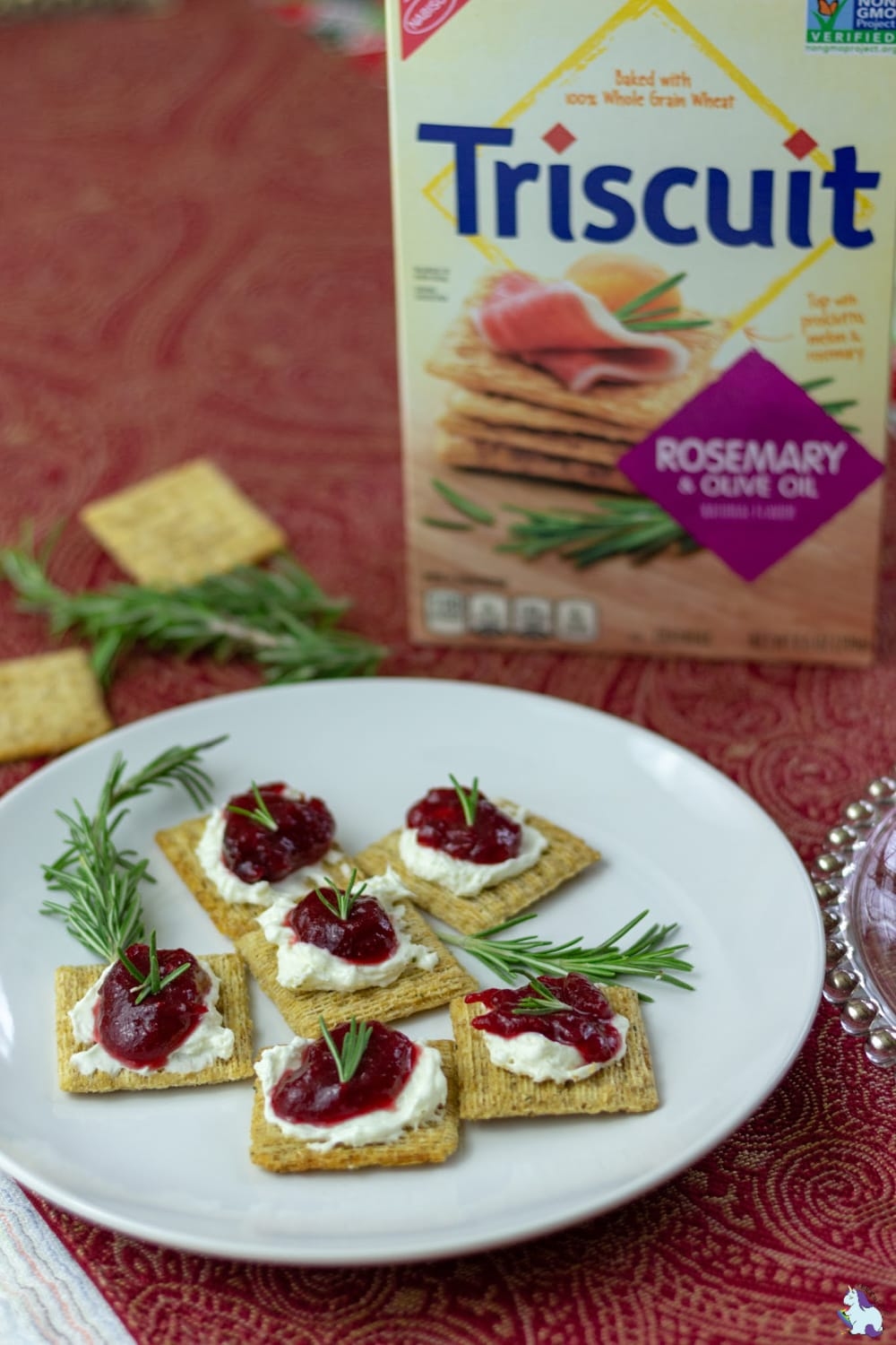 Triscuits with cranberry jam topping on a plate with a box of Triscuits