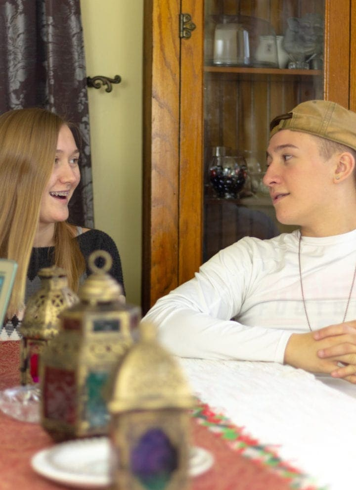two teens at the dining table answering questions about credit and finances