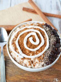 Smoothie bowl with cinnamon, yogurt swirl, raisins, and chia seeds.