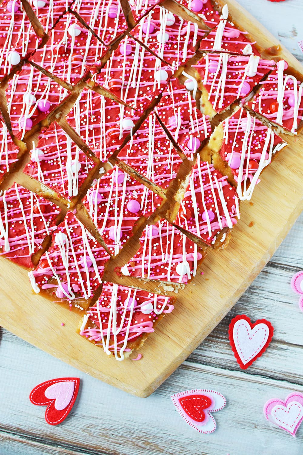 Cracker toffee candy on a board with Valentine's day decorations.