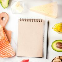 Ketogenic low carbs diet concept. Healthy balanced food with high content of healthy fats. Diet for the heart and blood vessels. Organic ingredients, white background, copy space top view, notepad