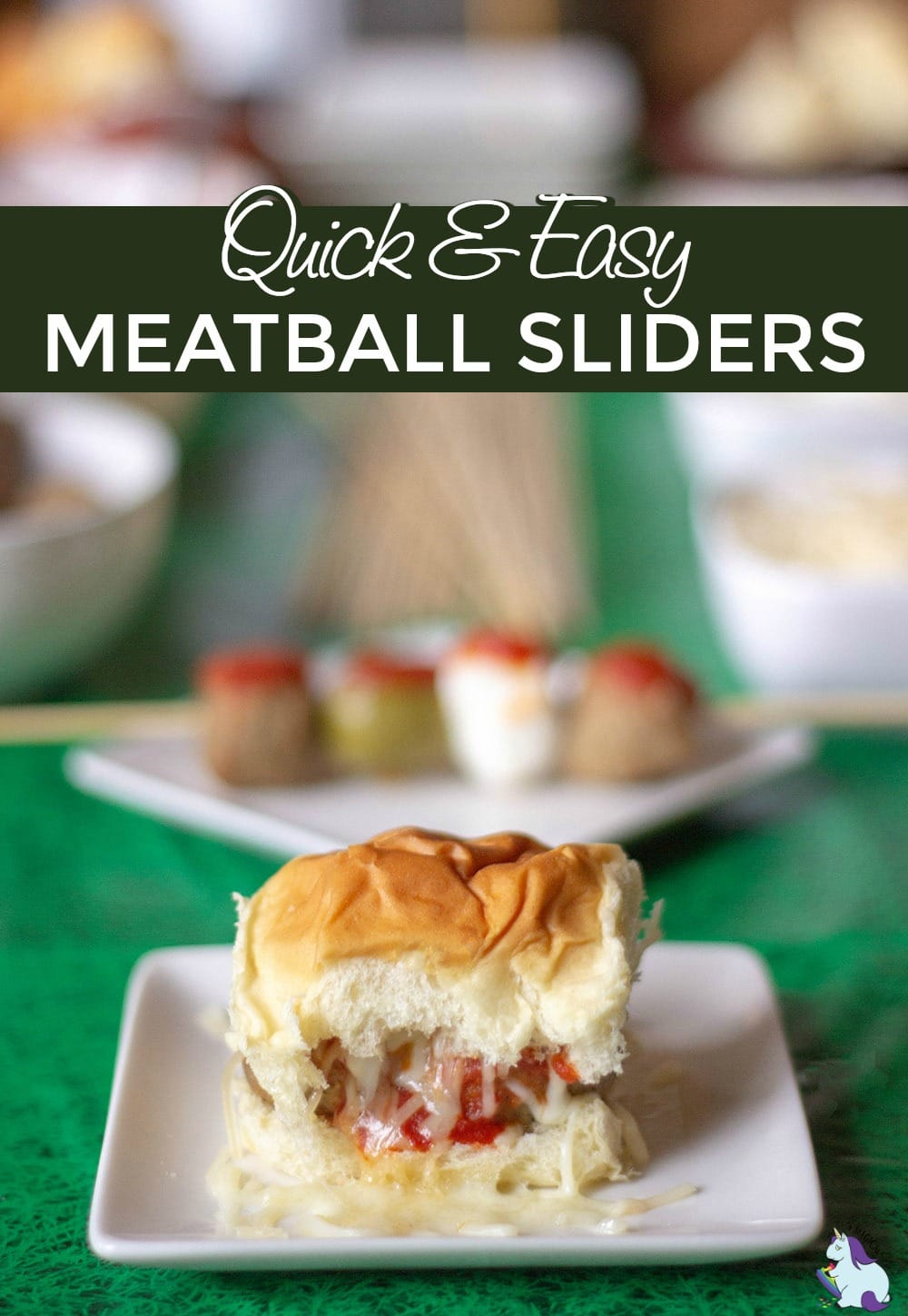 Meatball slider with cheese on a table decorated for game day.