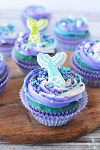 Mermaid cupcake sitting on a board with more cupcakes in the background.
