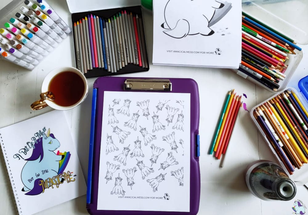 unicorn coloring pages on workspace with art supplies