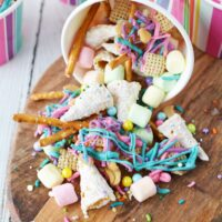 colorful unicorn snack mix spilling out of striped paper cup