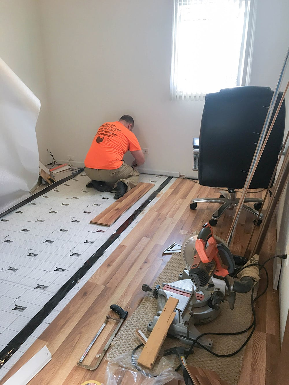 Husband installing new vinyl plank flooring.