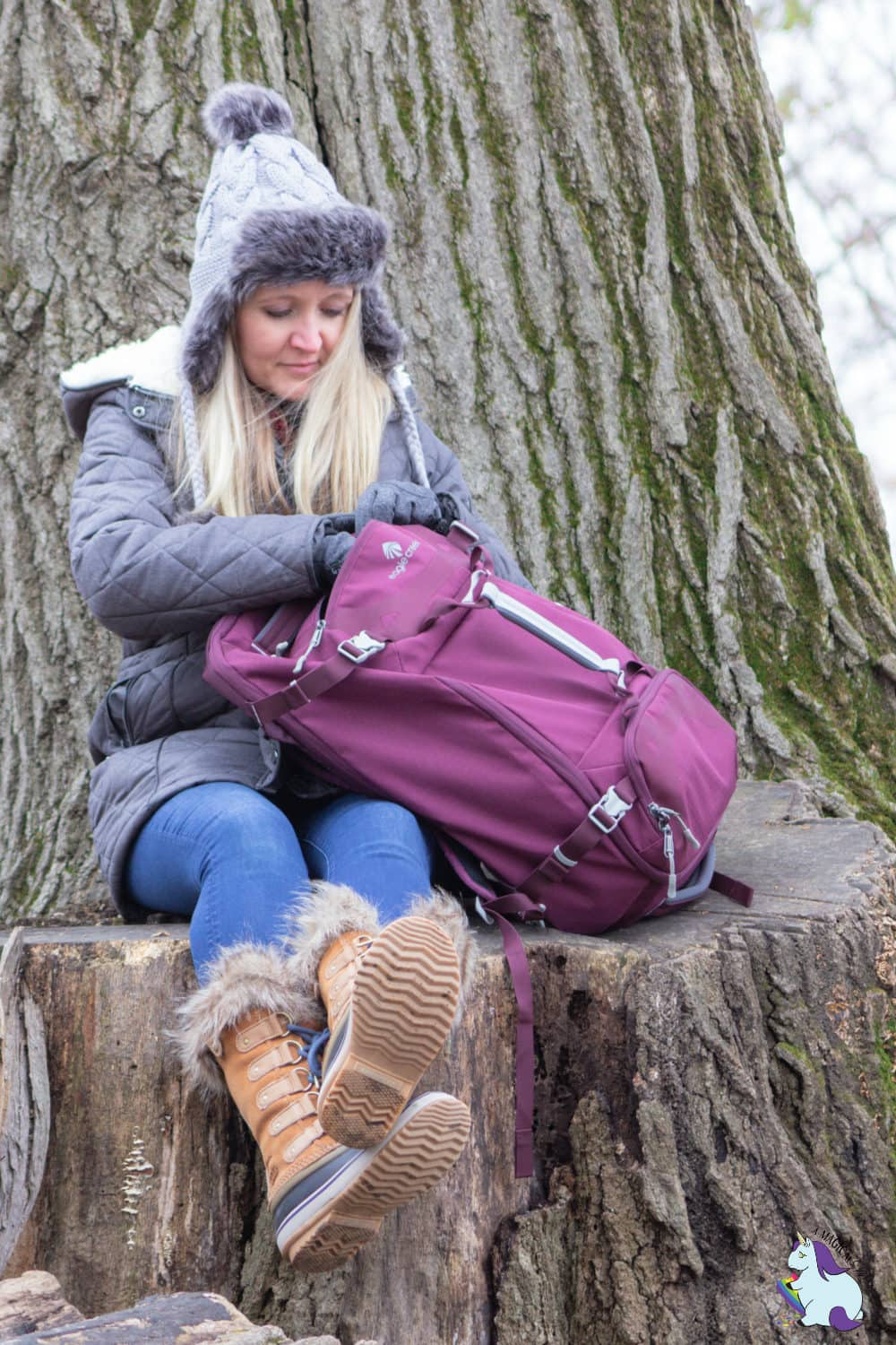 Shelley VanWitzenburg sitting on large tree stump with plum backpack