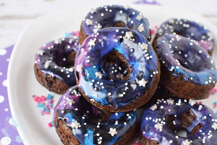 Galaxy donuts stacked on a plate.