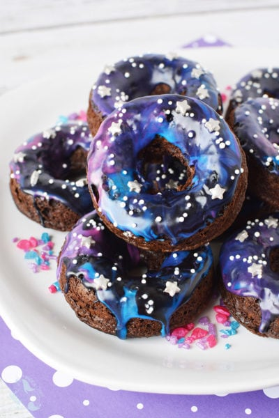 Galaxy donuts with star sprinkles stacked on a plate.