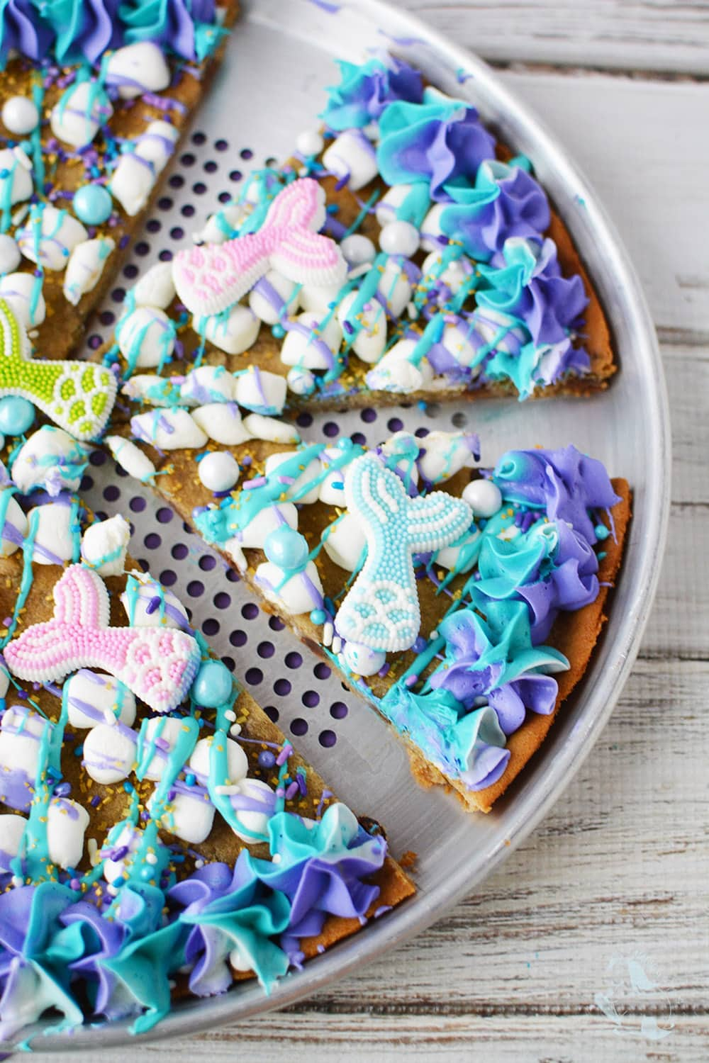 Mermaid cookie pizza sliced on baking pan