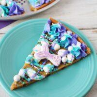 Mermaid dessert pizza sliced on a blue plate.