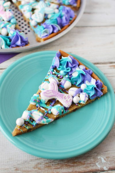 Mermaid dessert pizza sliced on a blue plate.