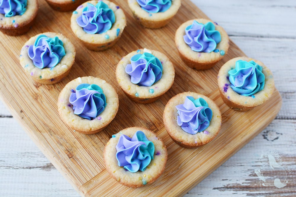 Filling cookie cups with purple and blue shades of frosting.