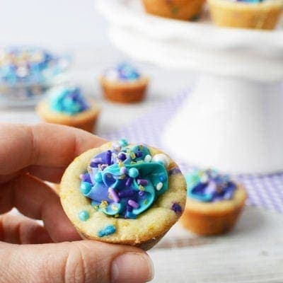 Holding a cookie cup filled with blue and purple frosting and sprinkles.