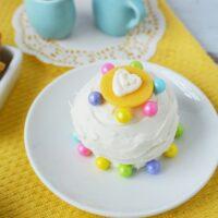 White mini cake on a plate with blue tea set.