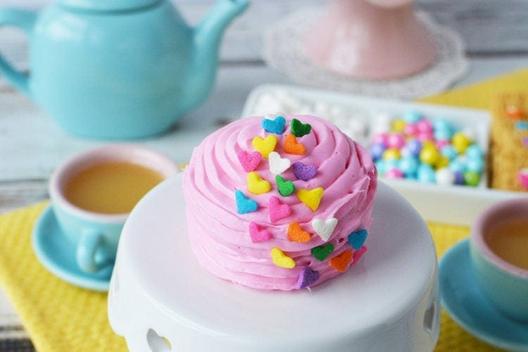 Pink fairy cake on a mini cake stand during a tea party.