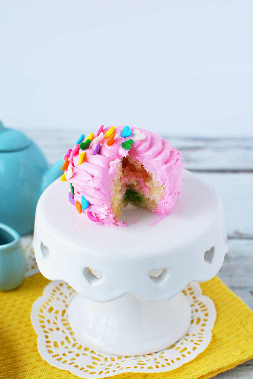 Pink mini cake with a slice cut from it.