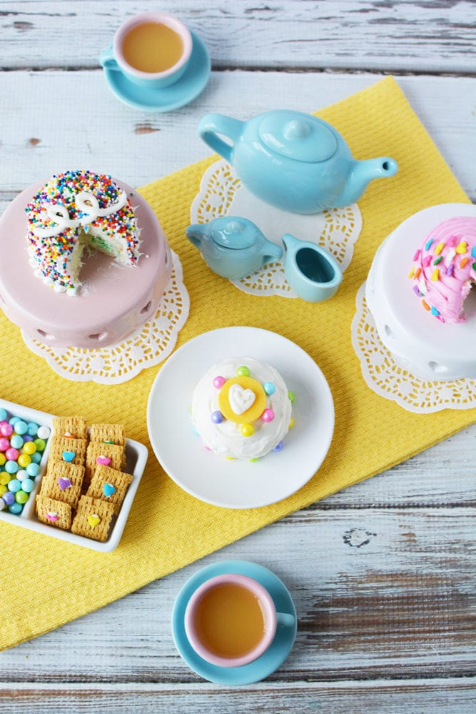 Overhead shot of a tea party with mini cakes