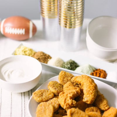 Nuggets and strips in a bowl on a plate with gold settings.