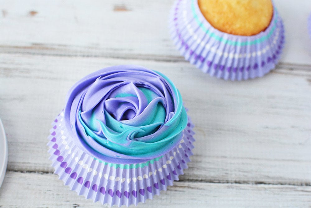 Blue and purple swirled frosting on a cupcake
