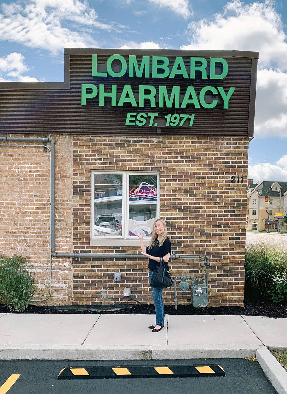 Standing in front of the Lombard Pharmacy.