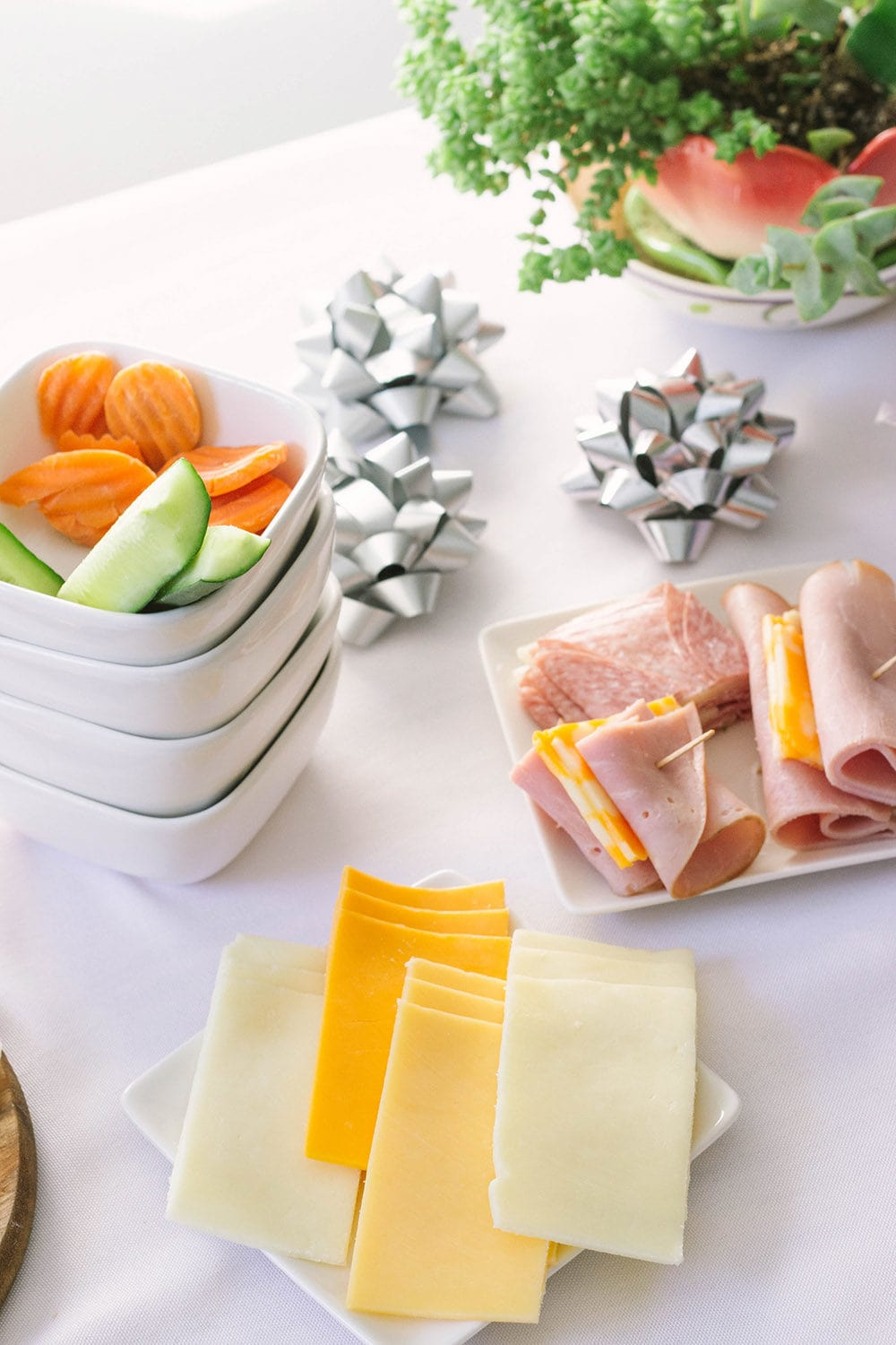 Cheeses on a plate, meat, and veggies on a table