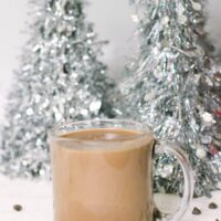Glass of low car hot chocolate in front of silver Christmas trees