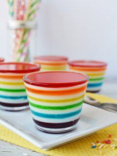 Cups of rainbow Jell-o layers on a table