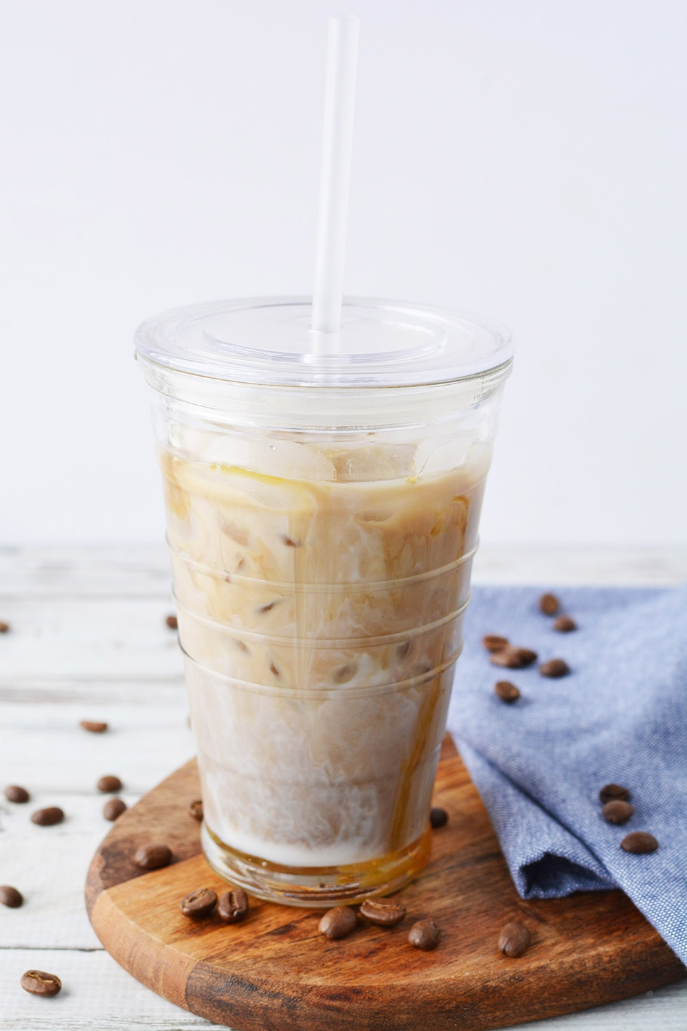 Iced coffee with caramel in a tumbler with straw