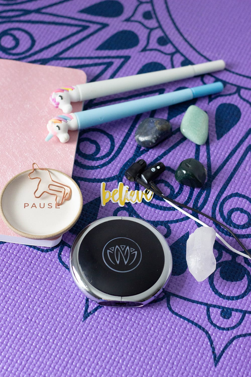 Relaxing items on a purple yoga mat