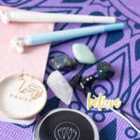 Unicorn pens, stones, and Zen unit on a yoga mat
