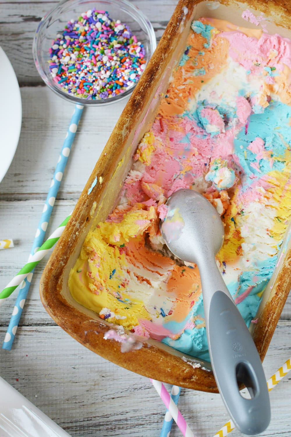 Pan of unicorn ice cream with scoops taken out