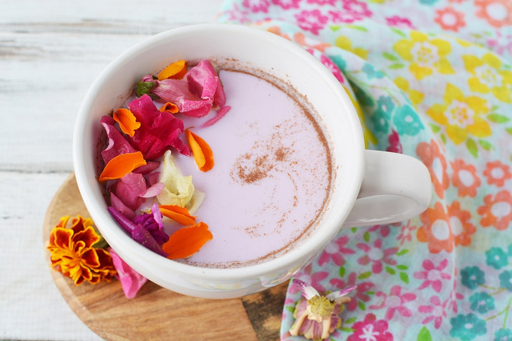 Mug of moon milk with edible flowers on top