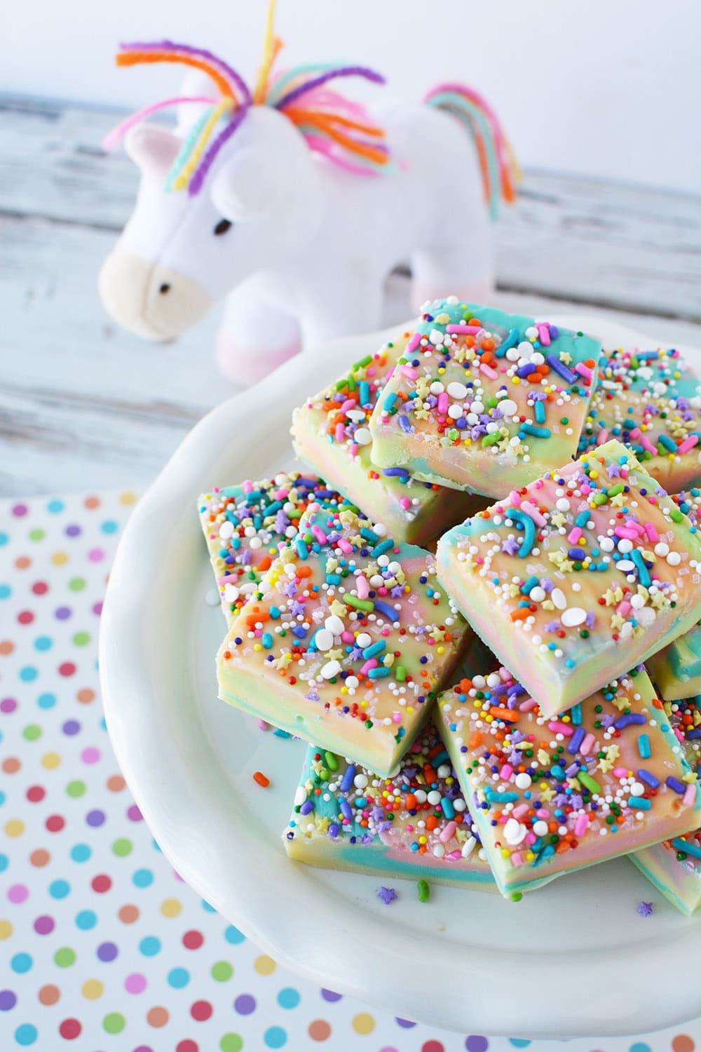 Unicorn fudge on a plate with a unicorn plush toy on the table