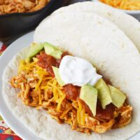 A plate of shredded chicken tacos with ranch and toppings