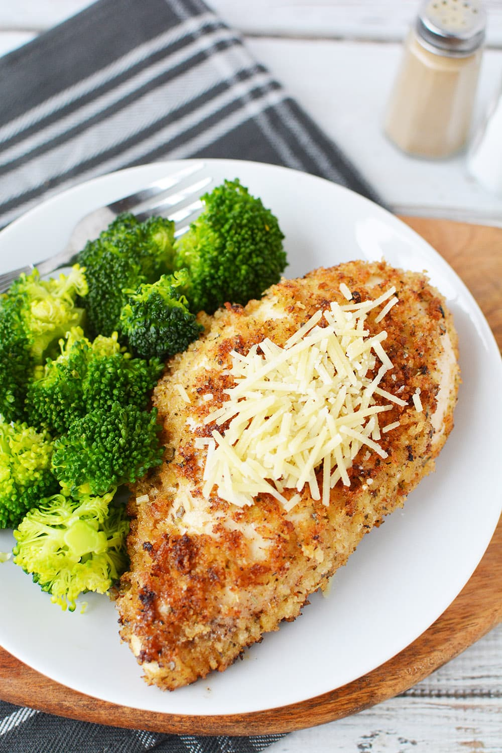 Plate of crispy chicken topped with parmesan and broccoli