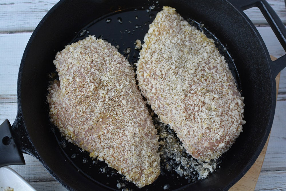 parmesan crusted chicken breast in pan frying