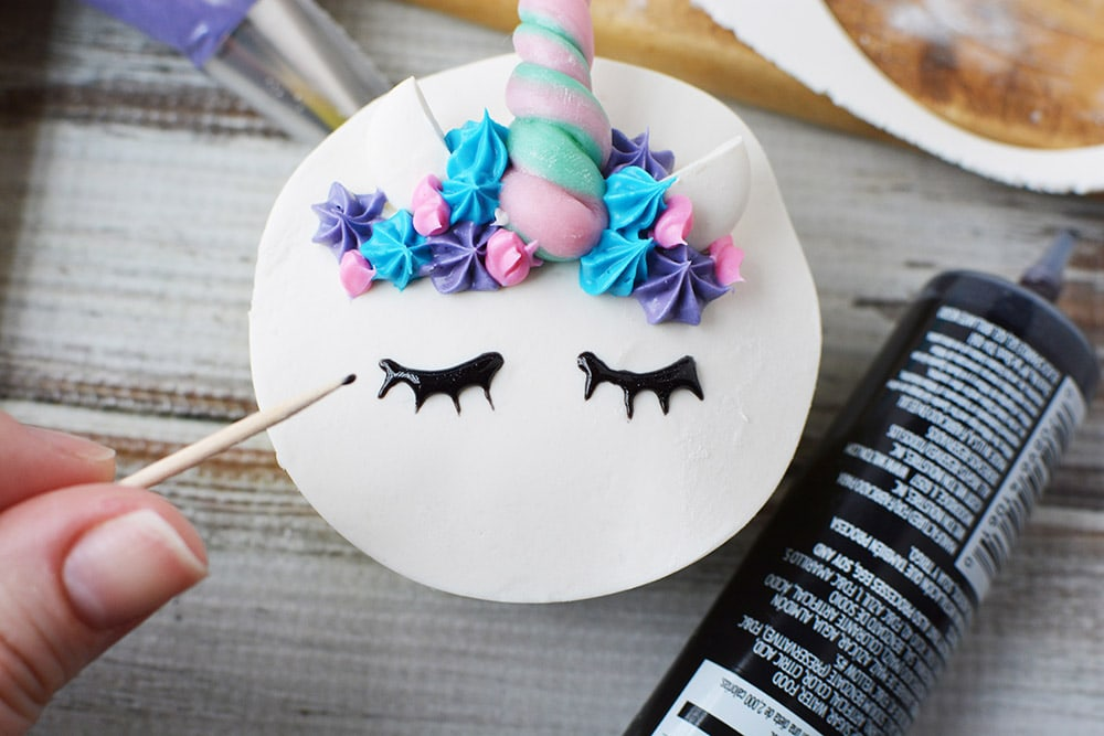 drawing eyes on unicorn cupcake